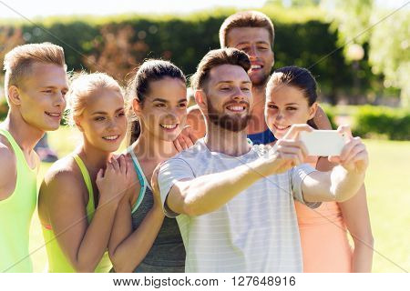 fitness, sport, friendship, technology and healthy lifestyle concept - group of happy teenage friends or sportsmen taking selfie with smartphone outdoors
