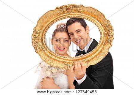 Young newlywed couple posing behind a vintage picture frame and smiling isolated on white background