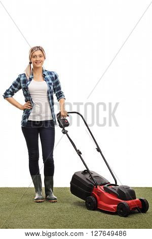 Vertical shot of a young woman posing with a lawnmower isolated on white background