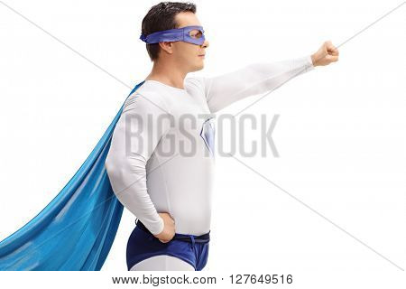 Profile shot of a young man in a superhero outfit holding a gripped fist in the air isolated on white background