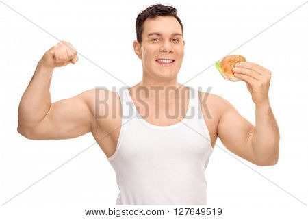Young man flexing his bicep and holding a sandwich in the other hand isolated on white background