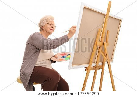 Elderly lady painting on a canvas with a paintbrush isolated on white background
