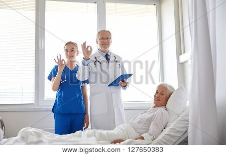 medicine, age, health care and people concept - doctor and nurse with tablet pc computer visiting senior patient woman and showing ok sign at hospital ward