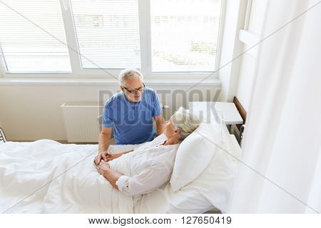 medicine, age, support, health care and people concept - happy senior man visiting and cheering his woman lying in bed at hospital ward