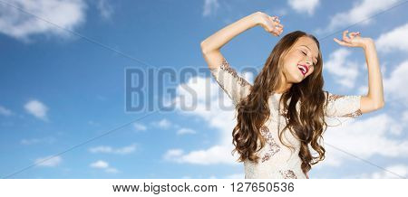 people, style, holidays and fashion concept - happy young woman or teen girl in fancy dress with sequins and long wavy hair dancing at party over blue sky and clouds background