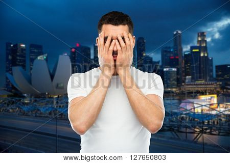 people, travel, tourism, emotions and stress concept - man in white t-shirt covering his face with hands over night singapore city background