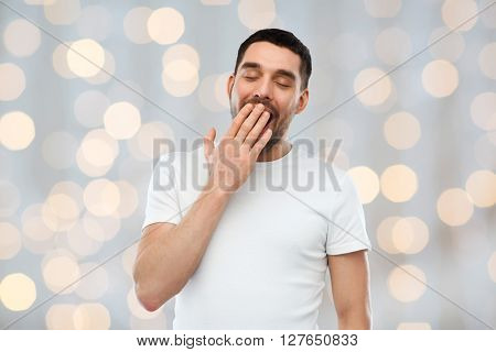 rest, bedtime and people concept - tired yawning man over holidays lights background
