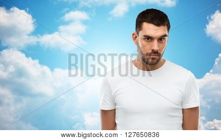 people concept - young man portrait over blue sky and clouds background