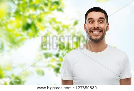 expression and people concept - man with funny face over green natural background