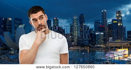 travel, tourism, expression and people concept - man thinking over night singapore city background
