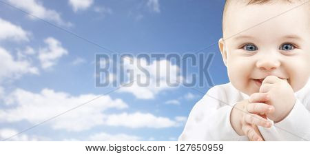 babyhood, childhood and people concept - happy baby face over blue sky background