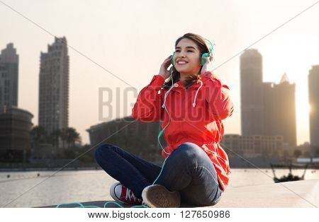 technology, travel, tourism and people concept - smiling young woman or teenage girl in headphones listening to music over dubai city street background