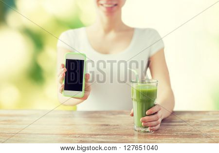 healthy eating, diet, detox, technology and people concept - close up of woman with smartphone green juice sitting at wooden table over green natural background