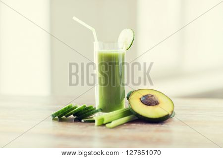 healthy eating, organic food and diet concept - close up of fresh green juice glass and vegetables on table