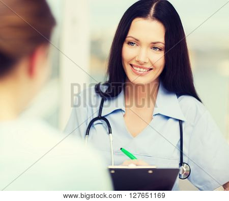 healthcare and medical concept - smiling female doctor or nurse with patient writing prescription