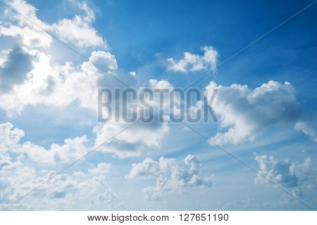 Blue sky and clouds with sun behind clous