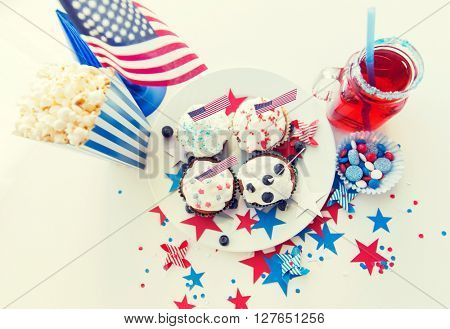 celebration, patriotism and holidays concept - close up of glazed cupcakes decorated with american flags, juice glass or mason jar, popcorn and candies at 4th july party on independence day