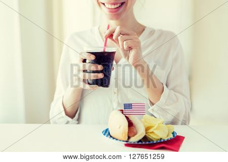 american independence day, celebration, patriotism and holidays concept - close up of happy woman drinking cola from plastic cup with hot dog and potato chips on 4th july at home party