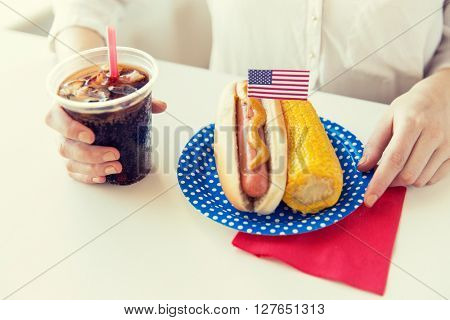 american independence day, celebration, patriotism and holidays concept - close up of woman hands with hot dog and corn holding cola drink in plastic cup on 4th july party