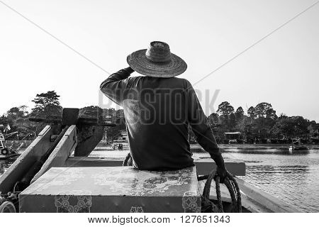 Rear view local fisherman guide holding rope, back and white