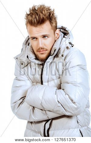 Young man in a winter jacket, he is cold. Isolated over white.