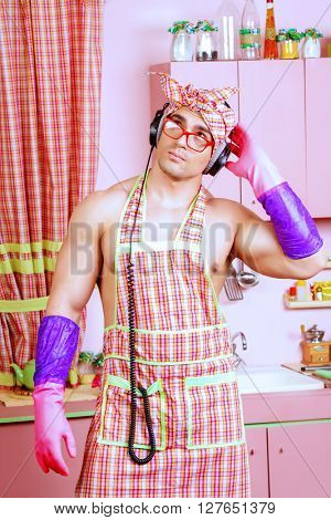 Funny and handsome muscular man in an apron takes a break from household chores, listening to music on headphones. Valentine's day. Women's day.
