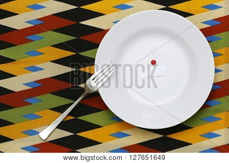 Diet concept - Empty plate with blank paper and red candy on the colorful background