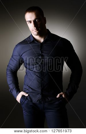 Fashion portrait of young masciline man posing over dark background.