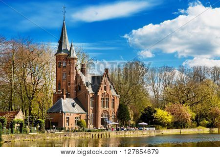 Bruges, Belgium - April 10, 2016: Minnewater lake, gothic building and people in cafe near Castle de la Faille, cloudy blue sky, Bruges, Belgium