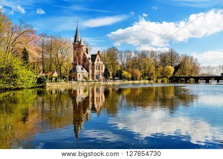 Bruges, Belgium - April 10, 2016: Minnewater lake panorama, reflection of gothic building and people in cafe near Castle de la Faille, cloudy blue sky, Bruges, Belgium