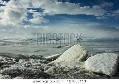 Ice floes in front of frozen glacier lake and mountain panorama in Iceland