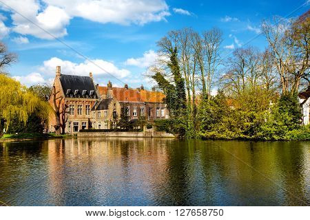 Bruges, Belgium - April 10, 2016:  Beautiful view in Bruges, Belgium at Lake of Love, or Minnewater, medieval houses against blue sky