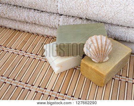Three homemade soap bars scallop shell and terry towel on the bamboo mat