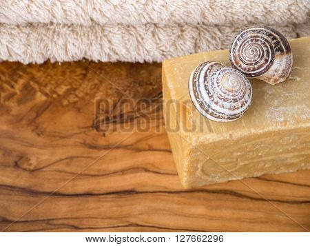 Homemade soap bar two snail shells and terry towel on the olive tree textured wooden board