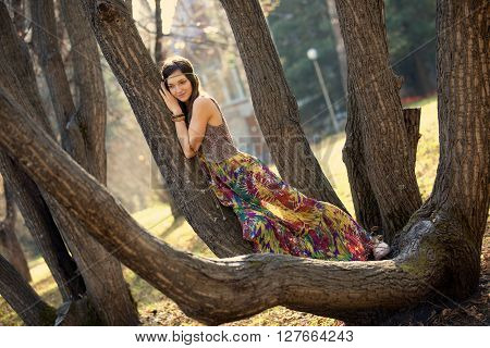 Hippie girl lying on the branches of a tree