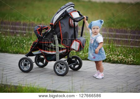 little funny girl with baby carriage outdoors