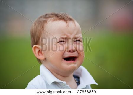 photo of cute little crying boy outdoors