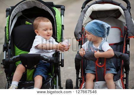 little funny boy gives water bottle to girlfriend