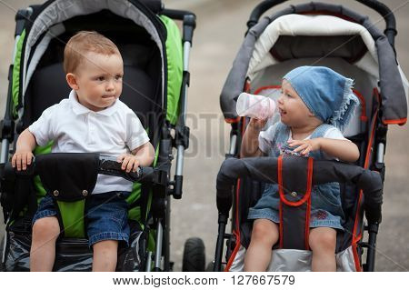 cute baby drinks juice sitting in baby carriage outdoors