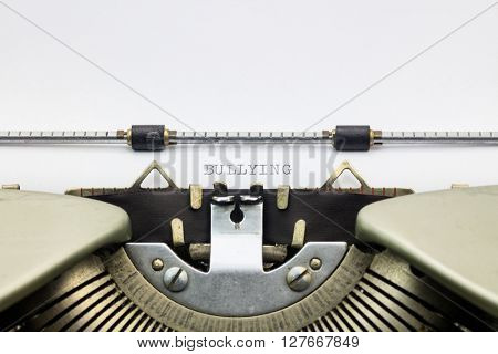Close-up of word Bullying on typewriter sheet