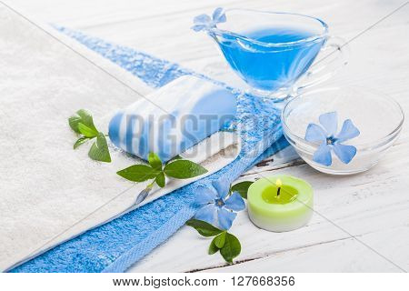 Spa still life of sea salt and essential oils and periwinkle flowers