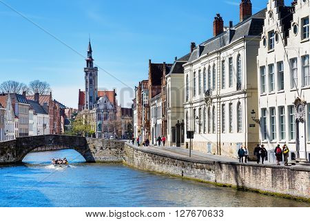 Bruges, Belgium - April 10, 2016: Canal and bridge view, boat with tourists, colorful houses and church tower in popular belgian destination