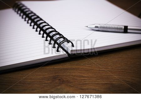 Black Spiral Bound Notebook On Wooden Background
