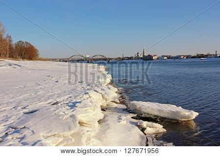 Spring landscape on the banks of the Volga river in Rybinsk. In the foreground and the melting ice floes in the background the bridge and Transfiguration Cathedral.