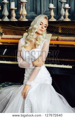 Healthy wedding hair. Gorgeous bride with long blonde curly hairstyle and bridal makeup on background of piano. Beauty indoor portrait. Attractive woman looking away