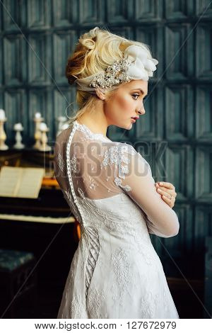 Attractive fashionable bride. Blonde hair. Hairdresser salon stylist trendy bright make-up. Pretty woman posing on background of piano looking away. Stylish hair accessories. Close up portrait