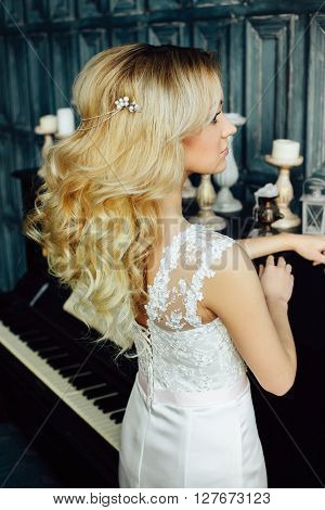 Fashion close up portrait of attractive young bride with long curly hair in morning of wedding day. Hairstyle. Glamour Makeup. Fashionable blonde girl posing on background of the piano looking away