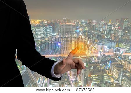 Business man touching an imaginary screen with cityscape