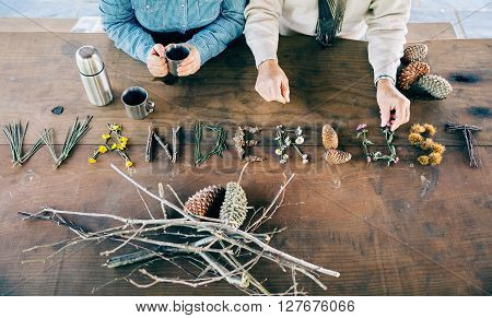 Senior couple holding coffee cups and making wanderlust word with natural objects over wooden table