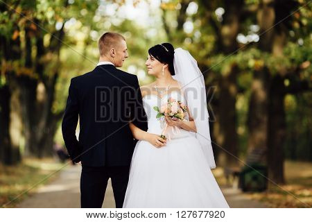 Beautiful bride and handsome groom at wedding day lovely hugging outdoors on nature. Bridal couple happy newlywed woman and man embracing in green park. Loving wedding couple outdoor.